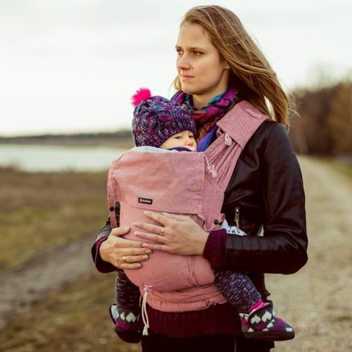 Junge Mutter mit einer Babytrage als Brusttrage