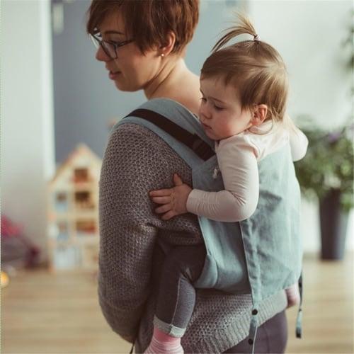 Mit mit einem Kleinkind in der Babytrage als Rückentrage
