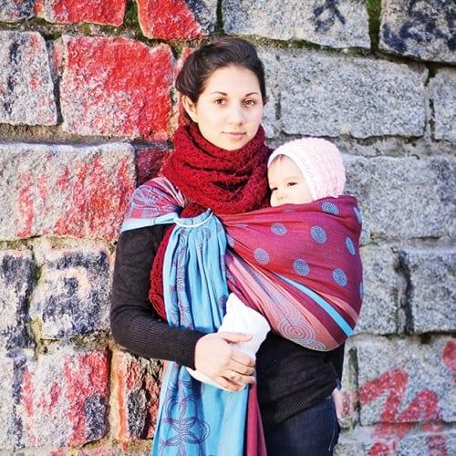 Junge Frau mit ihrem kleinen Baby in einem Tragetuch bei kalten Temperaturen im Winter