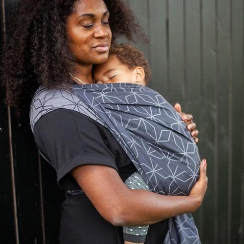 Mutter mit schlafendem Kleinkind in einem Tragetuch